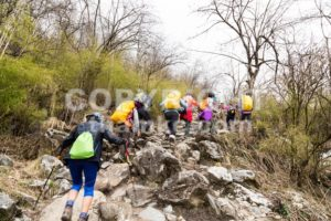 A group of people trekking an ascending rocky trail to the mountains of Annapurna, Nepal - ThamKC Royalty-Free Photos