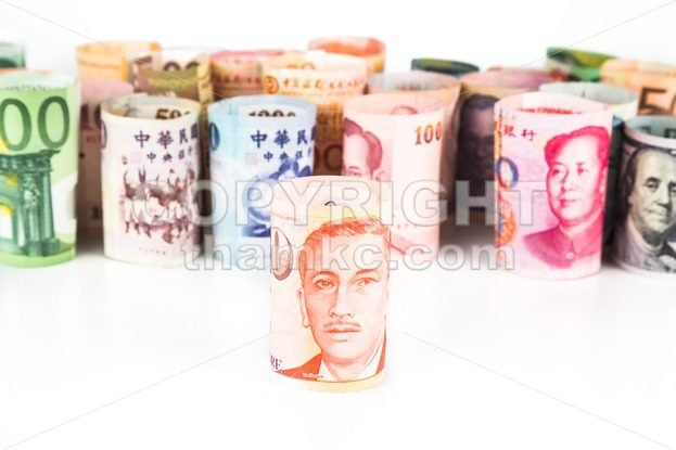 Pile of rolled-up currency notes with Singapore Dollar in front
