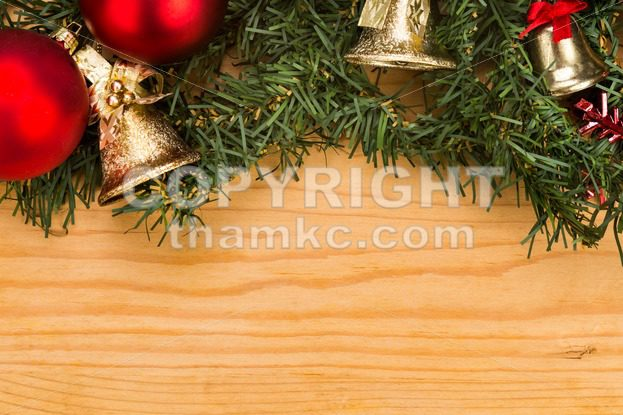 simple wooden christmas background with fir tree ornaments and bells