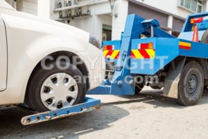 Tow truck towing a broken down car with focus on car being towed. - ThamKC Royalty-Free Photos