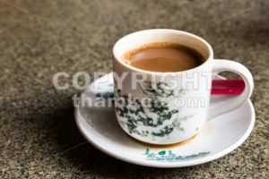 Traditional oriental Chinese coffee in vintage mug and saucer in soft focus setting with ambient light - ThamKC Royalty-Free Photos