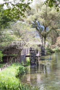 Ancient water wheel within serene and scenic river - ThamKC Royalty-Free Photos