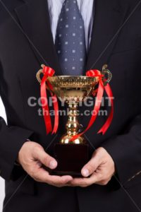 Asian business man in suit holding golden trophy - ThamKC Royalty-Free Photos