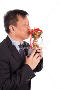 Asian business man in suit kissing golden trophy - ThamKC Royalty-Free Photos