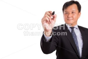 Asian business man in suit writing with marker pen - ThamKC Royalty-Free Photos