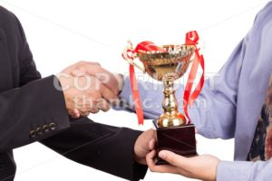 Asian business man shake hand and receive golden trophy - ThamKC Royalty-Free Photos