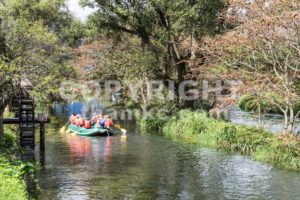 Group of people on raft peddling on serene scenic river - ThamKC Royalty-Free Photos
