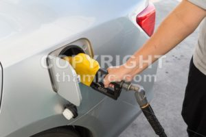 Hand with nozzle fueling unleaded gasoline into car - ThamKC Royalty-Free Photos