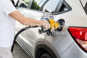 Person holding yellow nozzle filling petrol into car - ThamKC Royalty-Free Photos