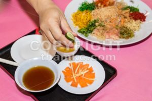 Person preparing Yee Sang or Yusheng Chinese delicacy - ThamKC Royalty-Free Photos