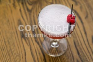 Red cocktail with cherry on table top - ThamKC Royalty-Free Photos