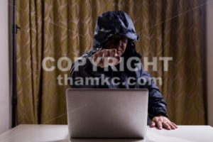 Angry Asian hacker pointing finger to audience while hacking network - ThamKC Royalty-Free Photos