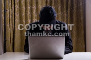 Asian businessman in suit attempting to hack computer network - ThamKC Royalty-Free Photos