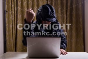 Asian hacker show fist while hacking computer network - ThamKC Royalty-Free Photos
