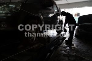 Silhouette of mechanic fixing car aligner onto car wheel - ThamKC Royalty-Free Photos
