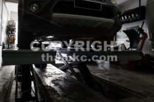 Silhouette of mechanics repairing car at small workshop garage - ThamKC Royalty-Free Photos