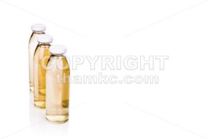 Three translucent liquid in glass bottle on white background - ThamKC Royalty-Free Photos
