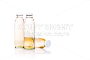 Translucent liquid in glass bottle on white background - ThamKC Royalty-Free Photos