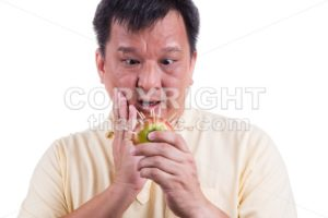 Conceptual of man holding apple with thorns fear suffer toothache - ThamKC Royalty-Free Photos