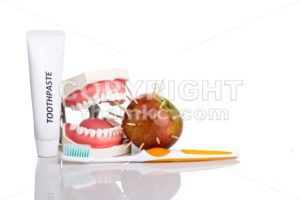 Conceptual of model mouth bite  apple with thorns, toothbrush, toothpaste, - ThamKC Royalty-Free Photos