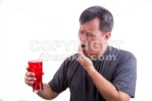 Focus on ice cold drink with man with toothache background - ThamKC Royalty-Free Photos