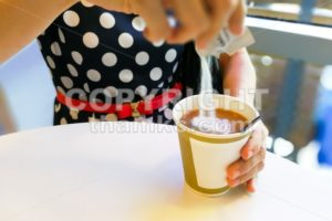Hand pouring unhealthy non dairy creamer from sachet into coffee - ThamKC Royalty-Free Photos