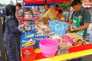 KUALA LUMPUR, MALAYSIA, May 29, 2016: Muslim shopper buying food from street vendor for breaking fast or iftar - ThamKC Royalty-Free Photos