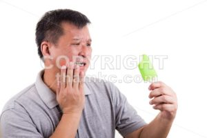 Matured man suffering intense toothache pain after biting ice cream - ThamKC Royalty-Free Photos