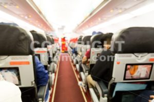 Defocused airplane cabin interior with seats and passengers - ThamKC Royalty-Free Photos
