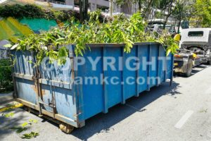 Garbage container latch with truck full of garden refuse woods - ThamKC Royalty-Free Photos