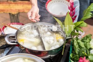 Hand adding ingredient into Asian steamboat pot meal - ThamKC Royalty-Free Photos