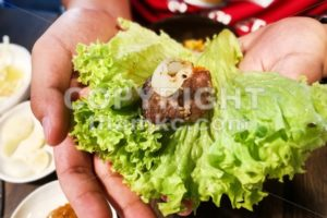 Hand holding korean barbecue beef and garlic wrap with salad - ThamKC Royalty-Free Photos