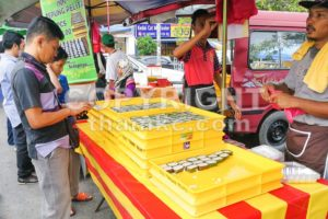 KUALA LUMPUR, MALAYSIA, June 2, 2017: Muslim shopper buying sweet desserts from street stall vendor for breaking fast or iftar - ThamKC Royalty-Free Photos