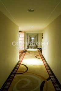 Long dark corridor with light from ceiling in vertical format - ThamKC Royalty-Free Photos