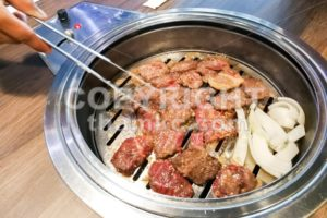 Person barbecue beef on bbq pit during korean meal set - ThamKC Royalty-Free Photos