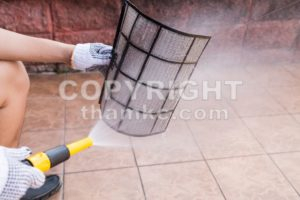 Person spraying water onto air conditioner filter to clean dust - ThamKC Royalty-Free Photos
