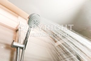 Shower head with refreshing water droplets spray in bathroom - ThamKC Royalty-Free Photos