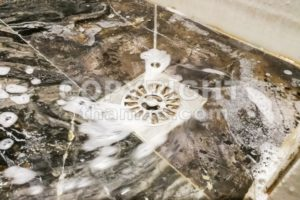 Soap foam and water flowing into bathroom drainage hole - ThamKC Royalty-Free Photos
