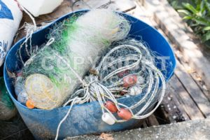 Traditional fisherman net, float and rope folded up - ThamKC Royalty-Free Photos
