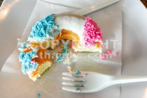 Unfinished donut glazed with sugar coating and sprinkles on plate - ThamKC Royalty-Free Photos