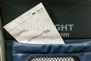 Air sickness bag tucked behind airplane seat pocket - ThamKC Royalty-Free Photos