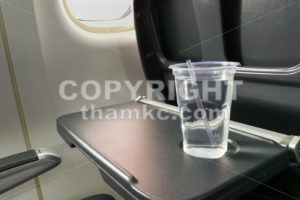 Disposable refreshing mineral water on table in air plane cabin - ThamKC Royalty-Free Photos