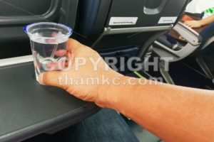 Hand holding disposable mineral water on table in air plane - ThamKC Royalty-Free Photos
