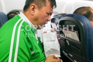 Nauseous air sickness Asian man vomiting into air sickness bag - ThamKC Royalty-Free Photos