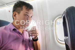 Person drinking water in airplane long haul flight to hydrate - ThamKC Royalty-Free Photos