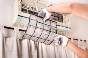 Technician pointing to air conditioner filter full of trapped dust - ThamKC Royalty-Free Photos