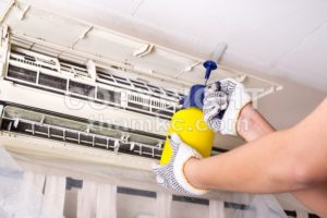 Technician spraying chemical water onto air conditioner grid to clean - ThamKC Royalty-Free Photos
