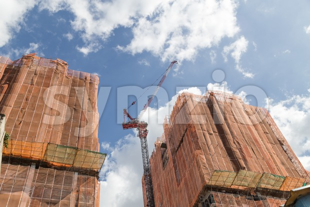 Tower crane  on buildings under construction with protective safety mesh Stock Photo