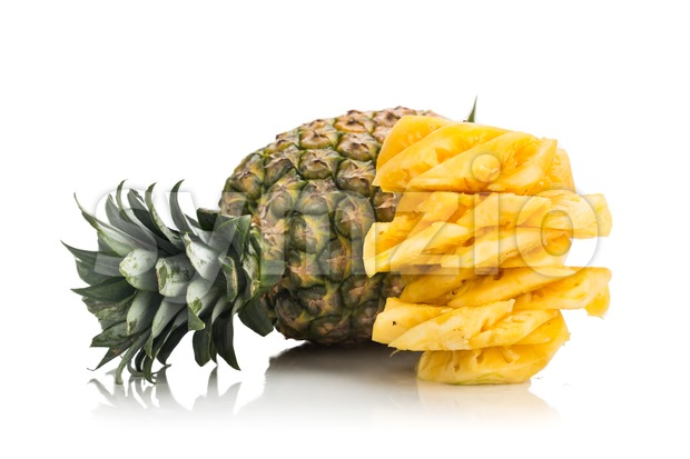 Fresh juicy nutritious cut pineapple with whole fruit as background. Stock Photo