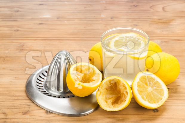 Freshly squeezed organic lemon juice with glass and squeezer. Stock Photo